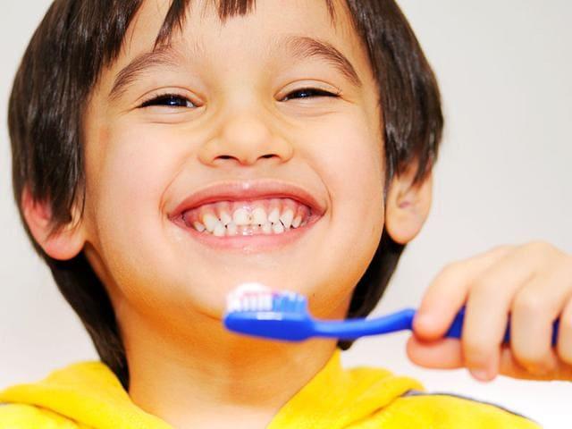 A smiling boy brushing his teeth