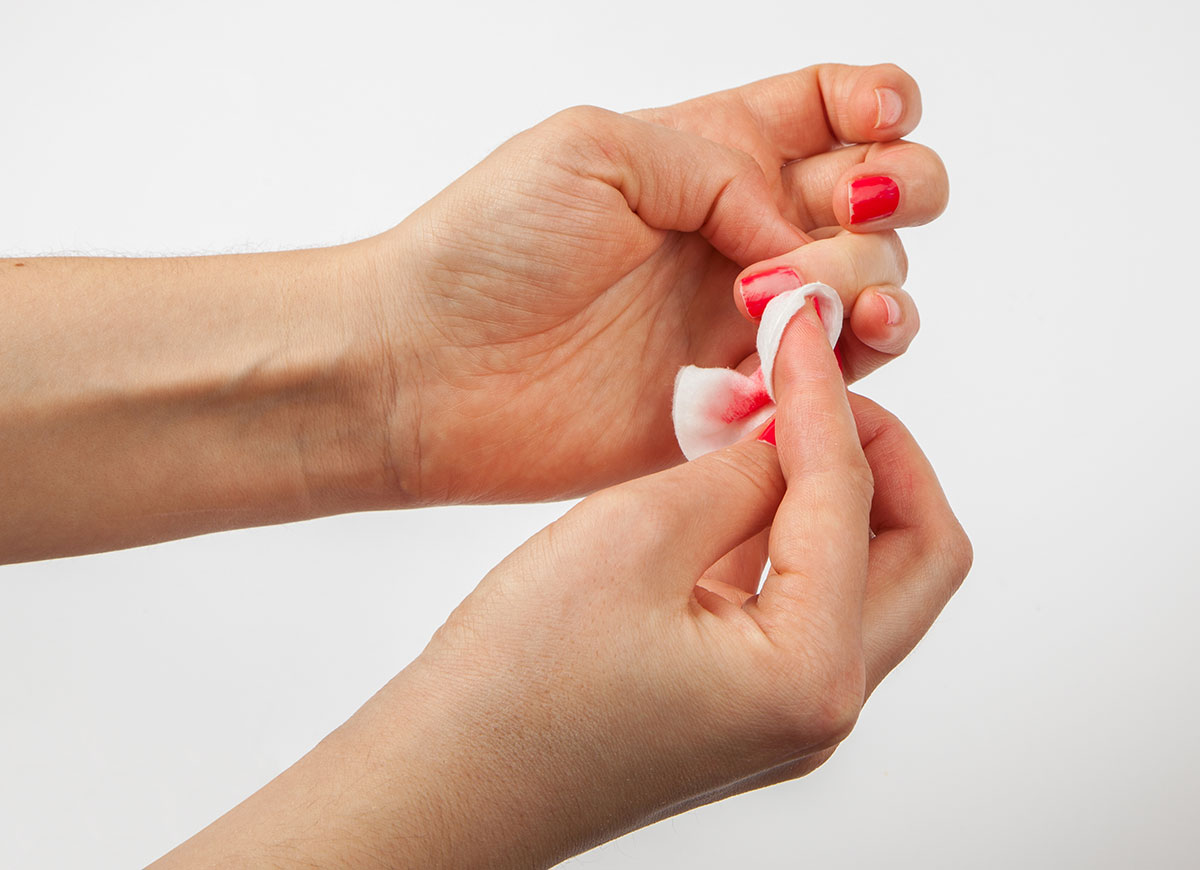 Girl removes the nail polish with cotton wool