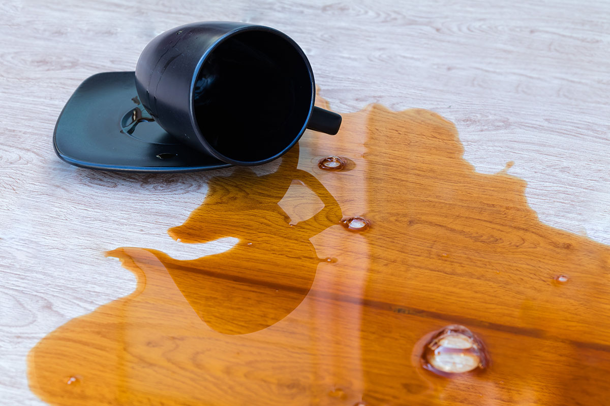 Closeup coffee spilled in a black cup on wooden floor