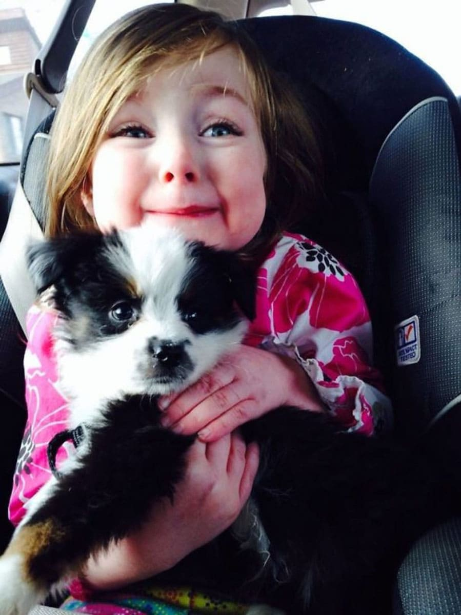 Girl smiling holding a puppy