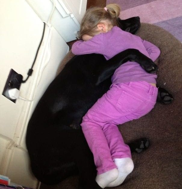 Girl and her dog hugging on the floor