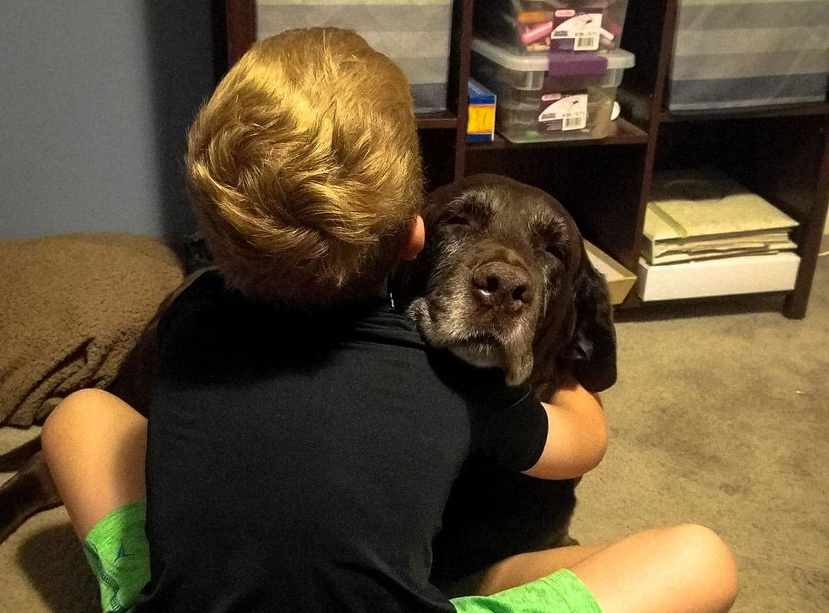 A boy and dog hugging