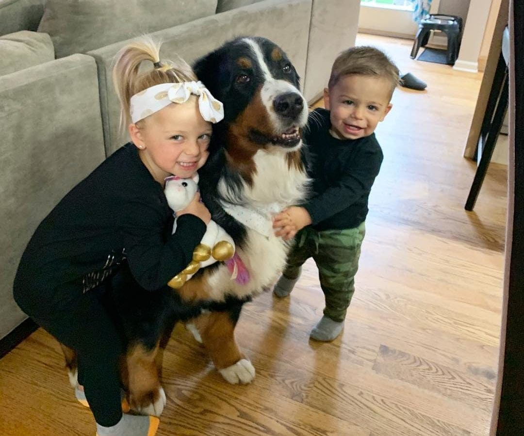 A brother and sister hugging their dog