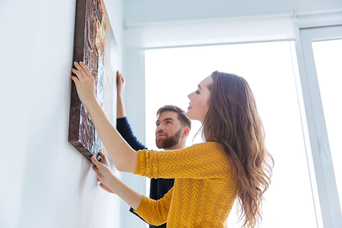 Couple hanging up a picture