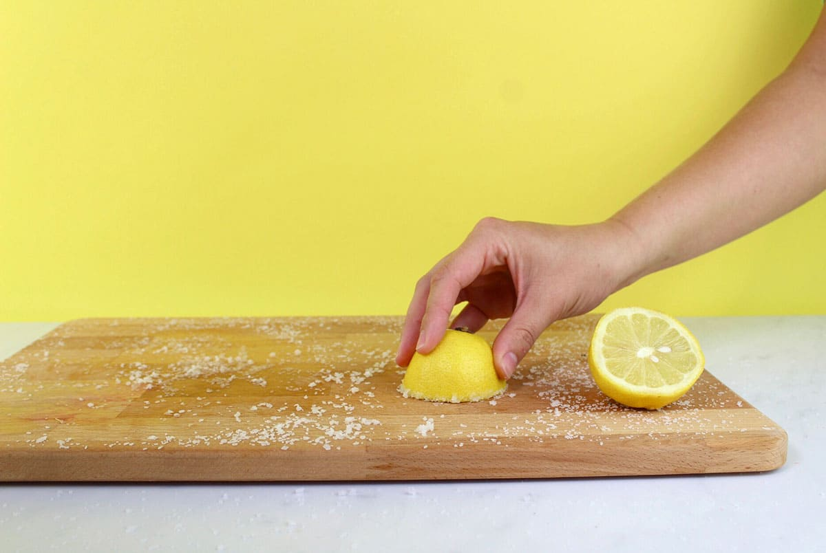 Someone cleaning a cutting board with salt and a lemon