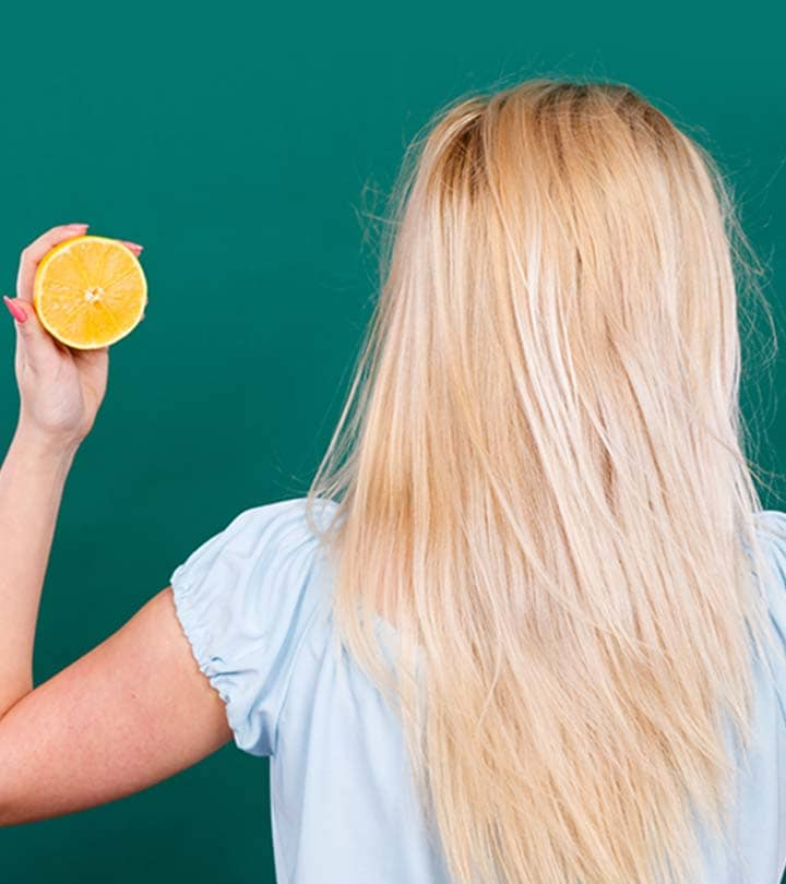 Woman holding a lemon next to her hair