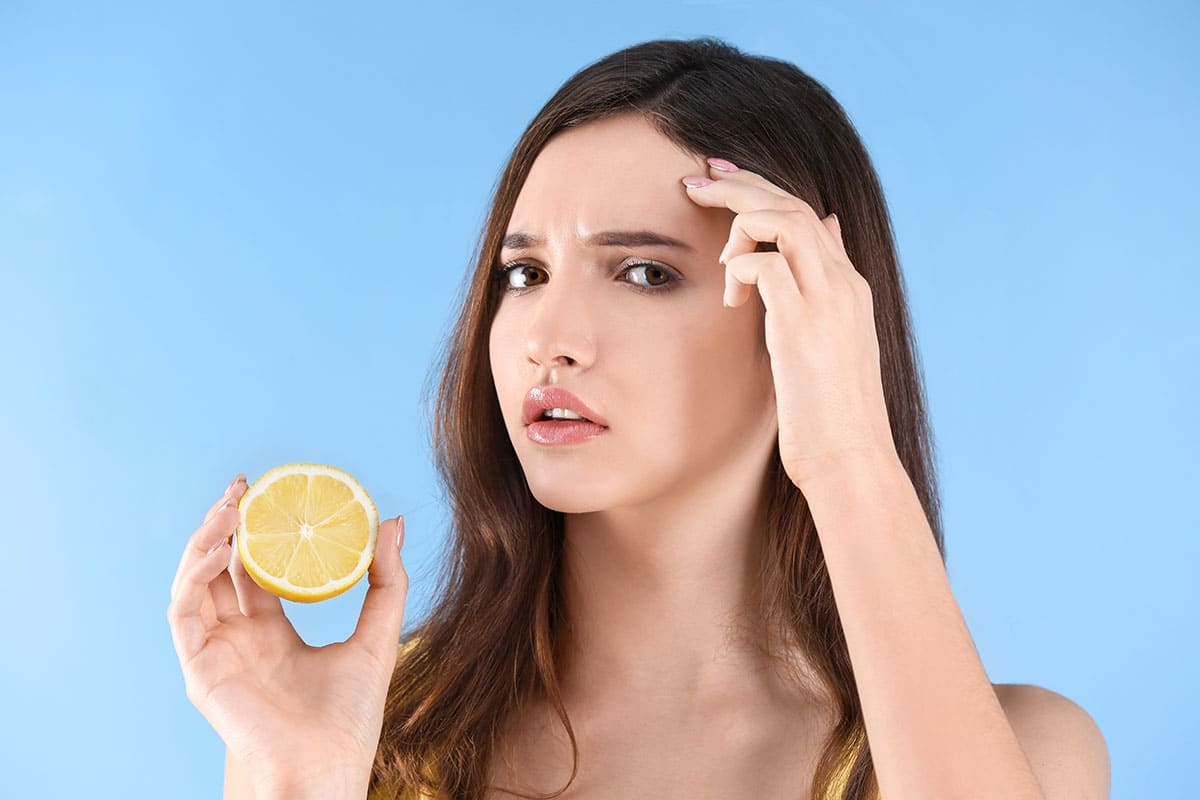 Teenage girl with acne problem holding lemon against color background