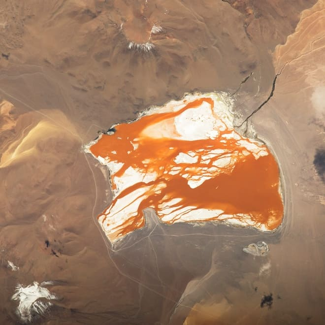 a picture captured in space; a view of the orange lake surrounded by dunes.
