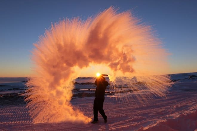 during the sunset, a man threw hot water in the Antarctician air, watching it instantly freeze above him
