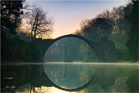 a semi-circle bridge reflecting off calm waters, resembling a complete circle