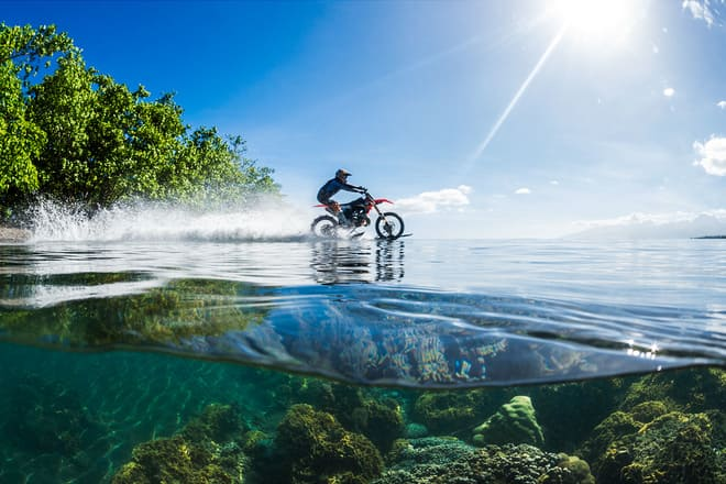 a beautiful picture was taken out in nature with bright, beautiful waters whiles a man drives his dirt bike across the water