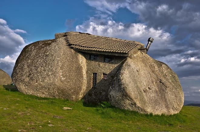 a house made out of rocks up on a mountain. The house looks like it had an allergic reaction to a bee sting.