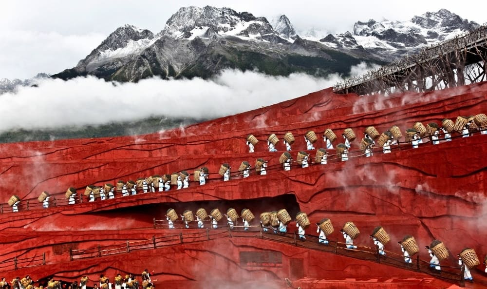 the beautiful picture is of a mountain covered in snow and clouds, with workers carrying baskets up red rampways to the top.