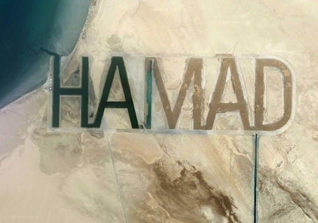 Skyview picture of a beach with the name 'Hamad' branded in the sand.