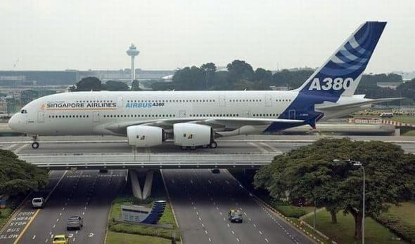 a picture of an airplane on a bridge which is on top of a highway.