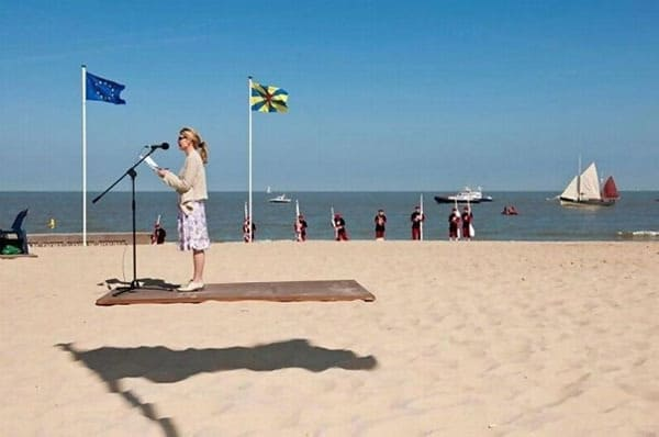 a woman is standing on a wooden stage on the beach, she appears to be levitating.