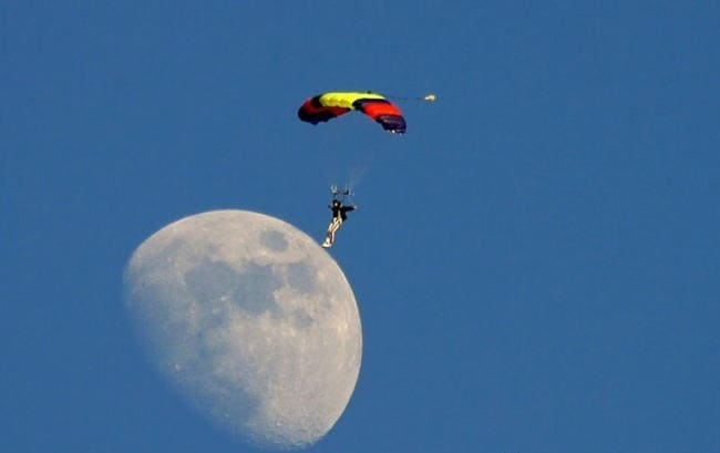 a perfectly timed shot of a man skydiving, seemingly landing on the moon.