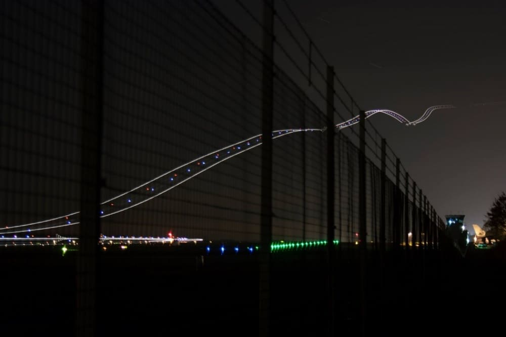 a picture captured at night, of a runway created by lights leading to the sky.