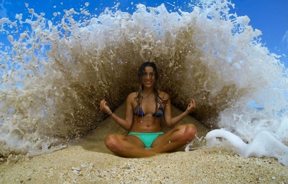 a woman sitting in a yoga position as a wave is about to hit her.