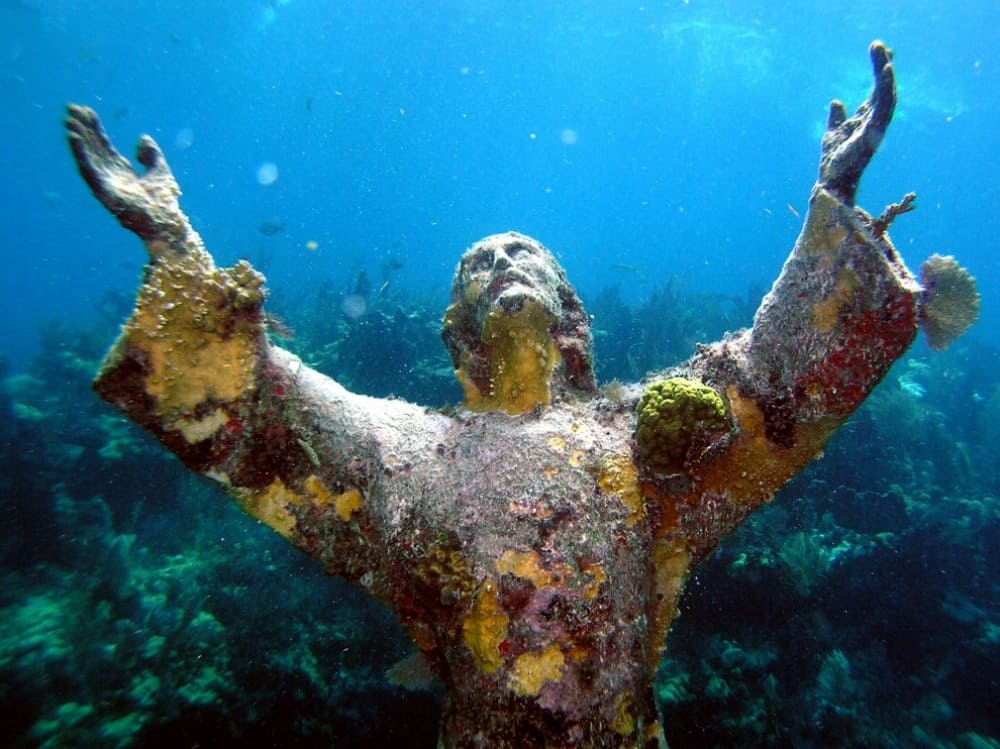 a statue of Jesus underwater, in the ocean covered in coral