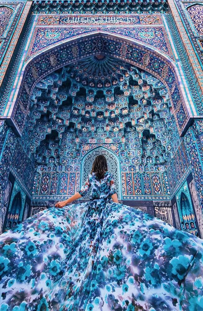 a lady wearing a blue dress is camouflaged with the blue walls of a mosque in front of her