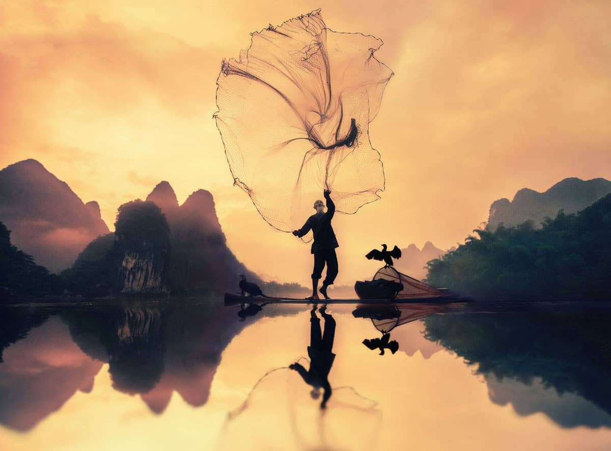 a man stands by the waterside with the sunset in the background, he throws a net into the air, and his reflection shines bright in the water.