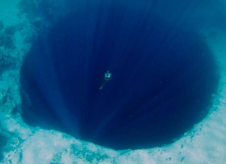 Diver in a big black hole in the ocean