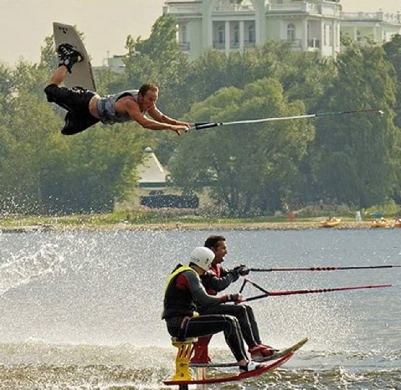 One wakeboarder flying above two water skiers on a lake