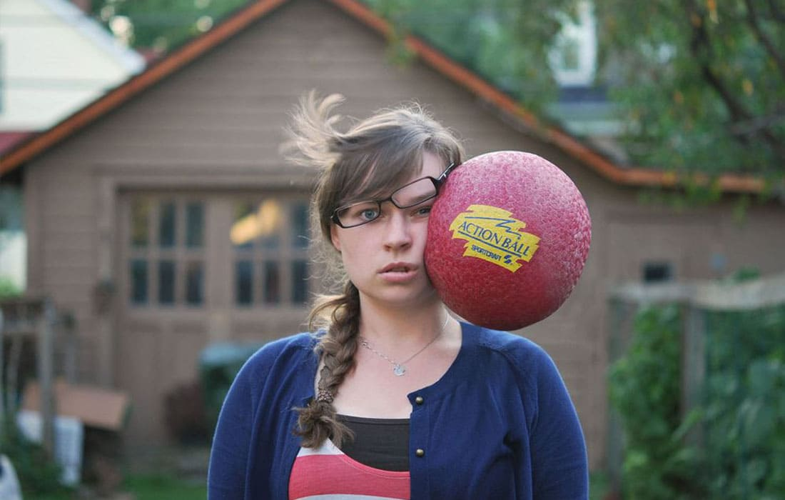 A girl being hit in the face with a ball