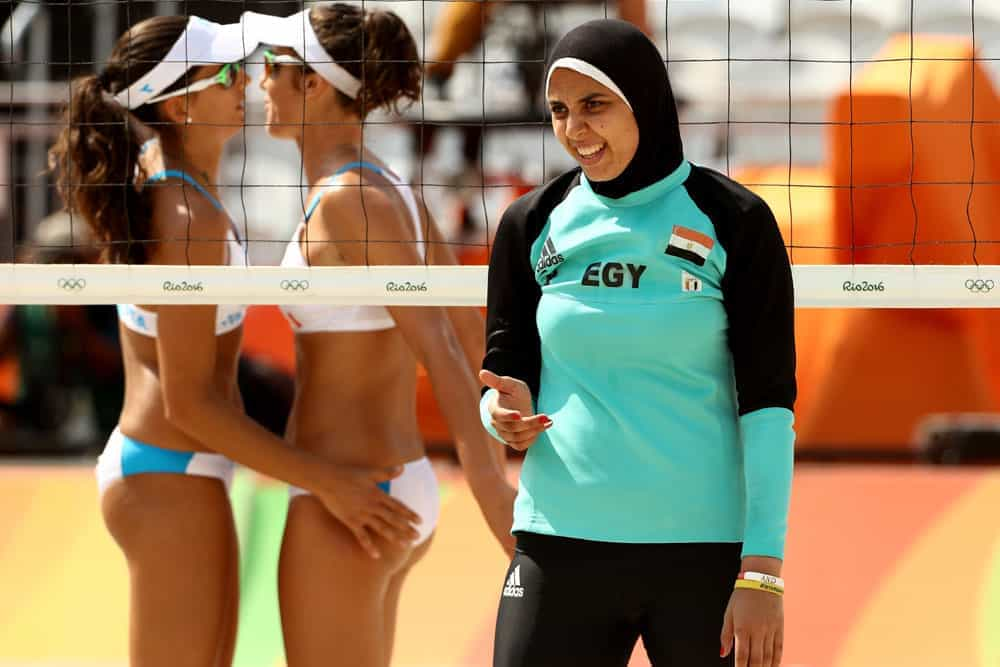 A Muslim volleyball player in front of two volleyball players