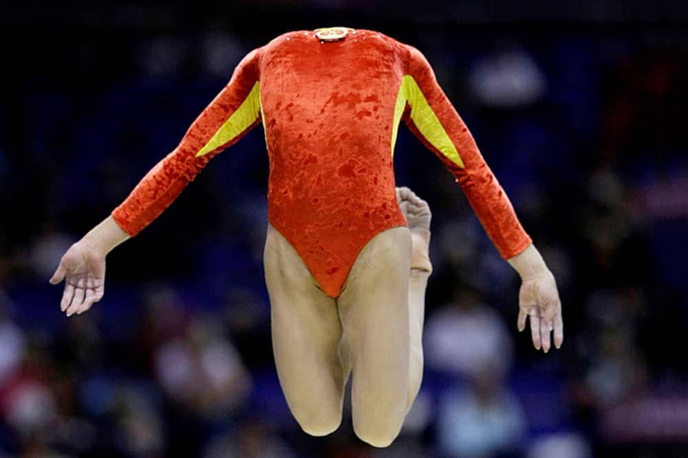 Gymnast jumping with her head bent back