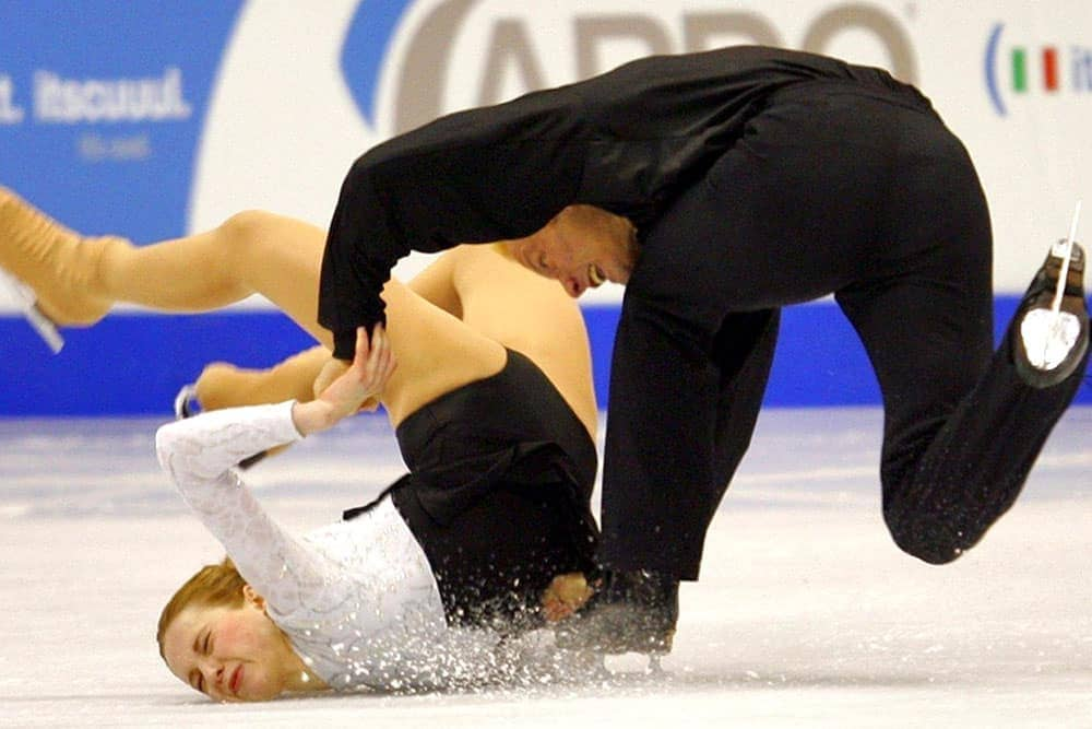 Two figure skaters falling on the ice