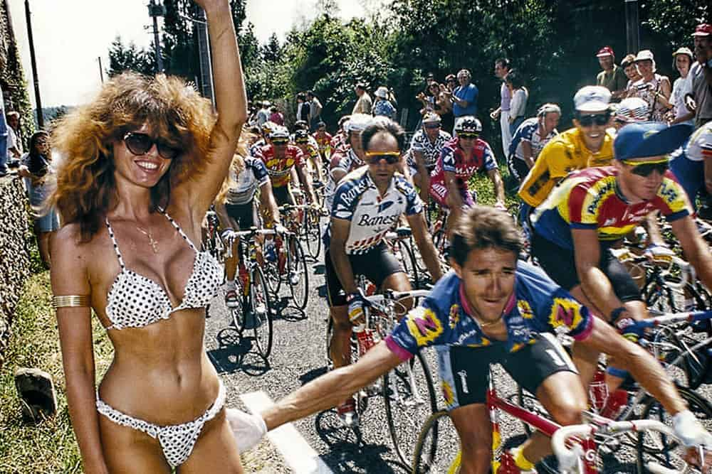 Woman in a bikini standing next to cyclists in a race