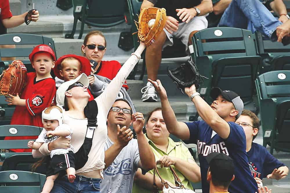 A woman holding a baby catching the baseball in the crowd