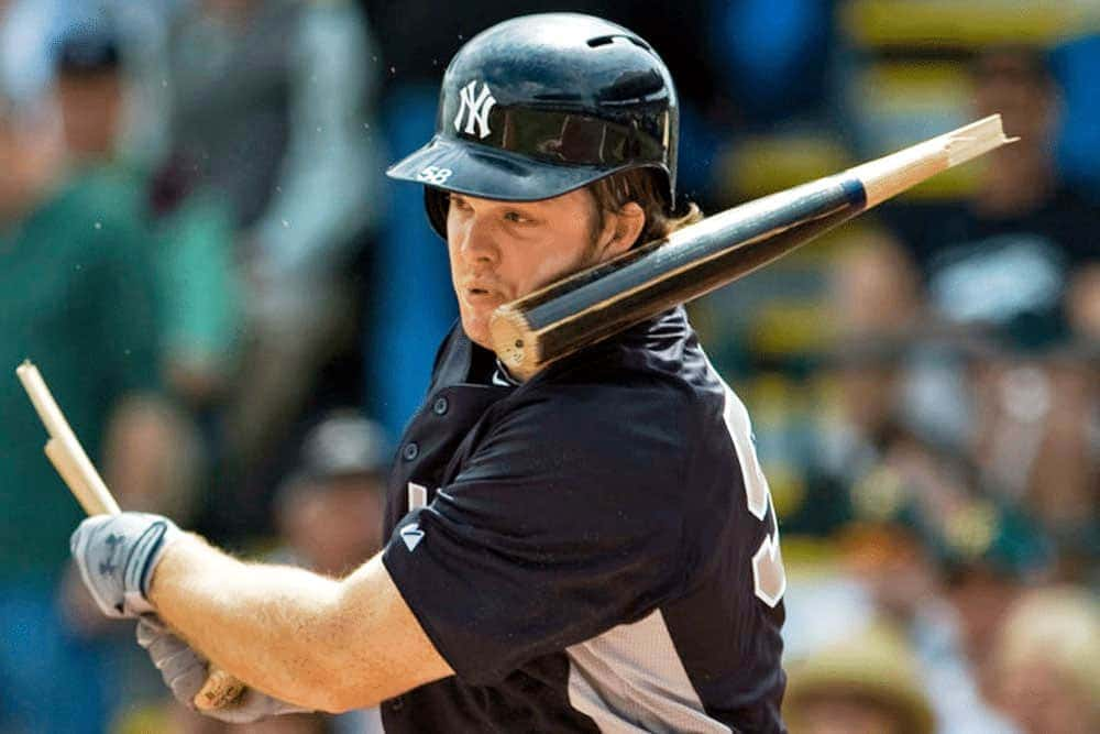Baseball player swinging a broken bat