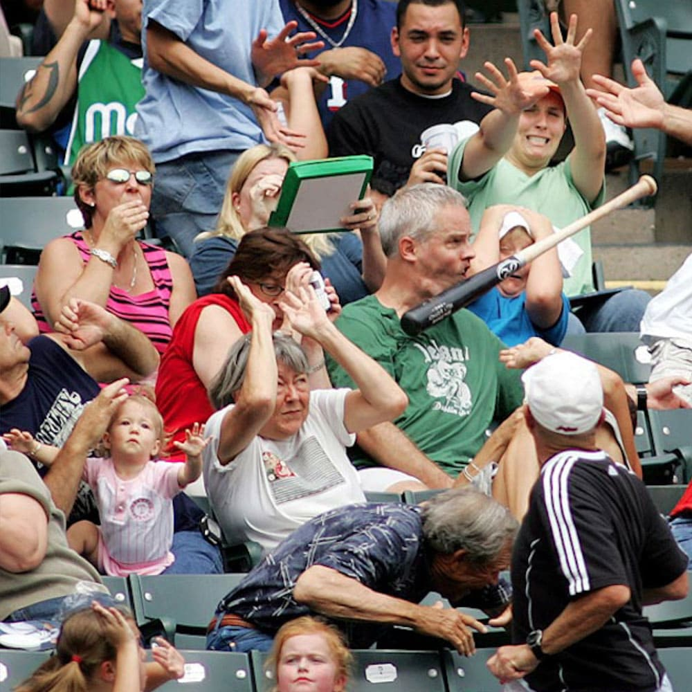 A man in a baseball crowd getting a bat to the face