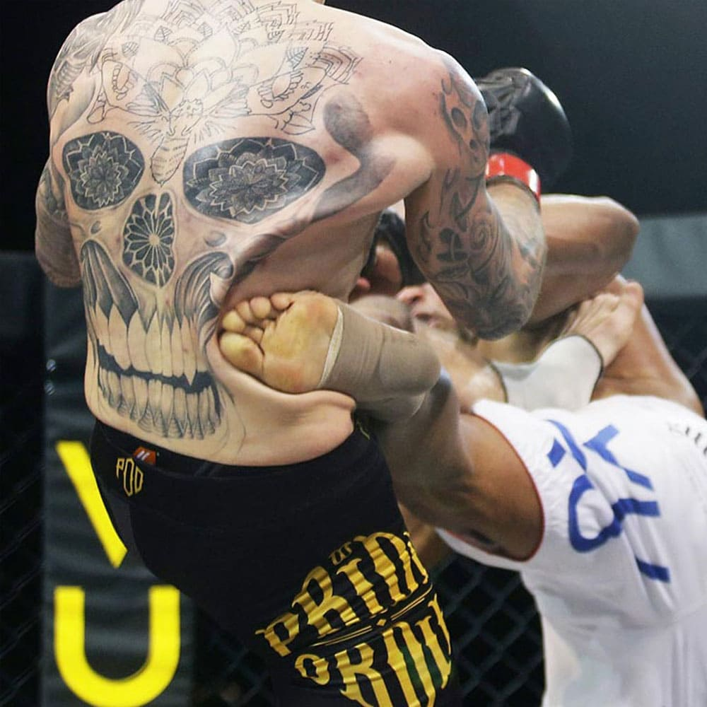 A man with a skull tattoo on his back is getting kicked in his side