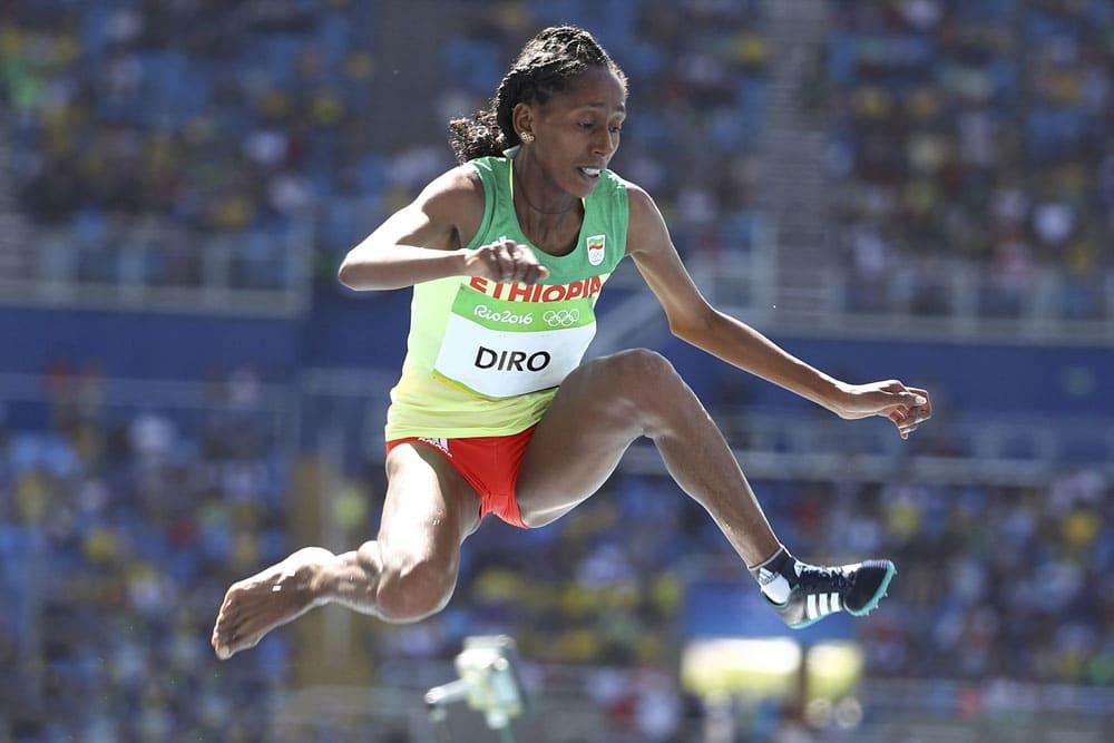 Etenesh Diro jumping a hurdle with one shoe