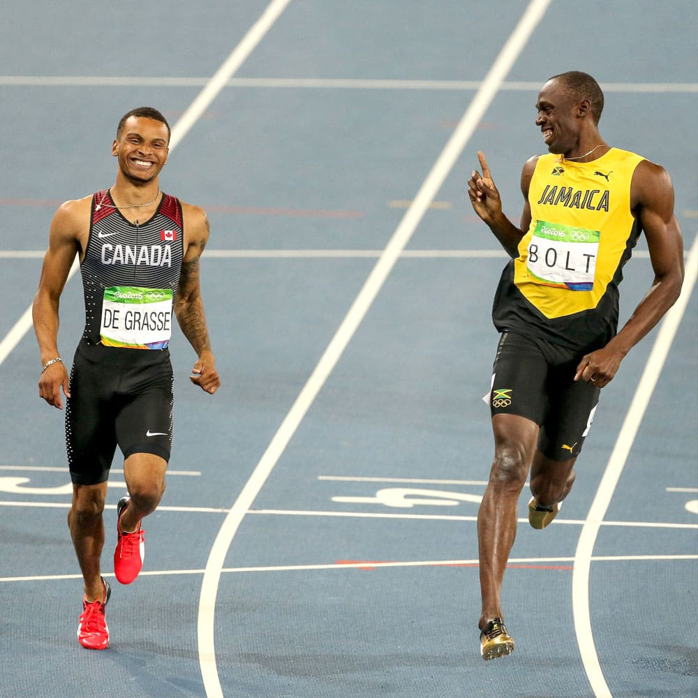 Andre De Grasse and Usain Bolt running on the track