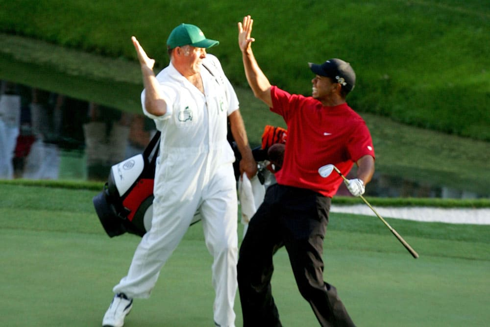 Tiger Woods high-fiving his caddie
