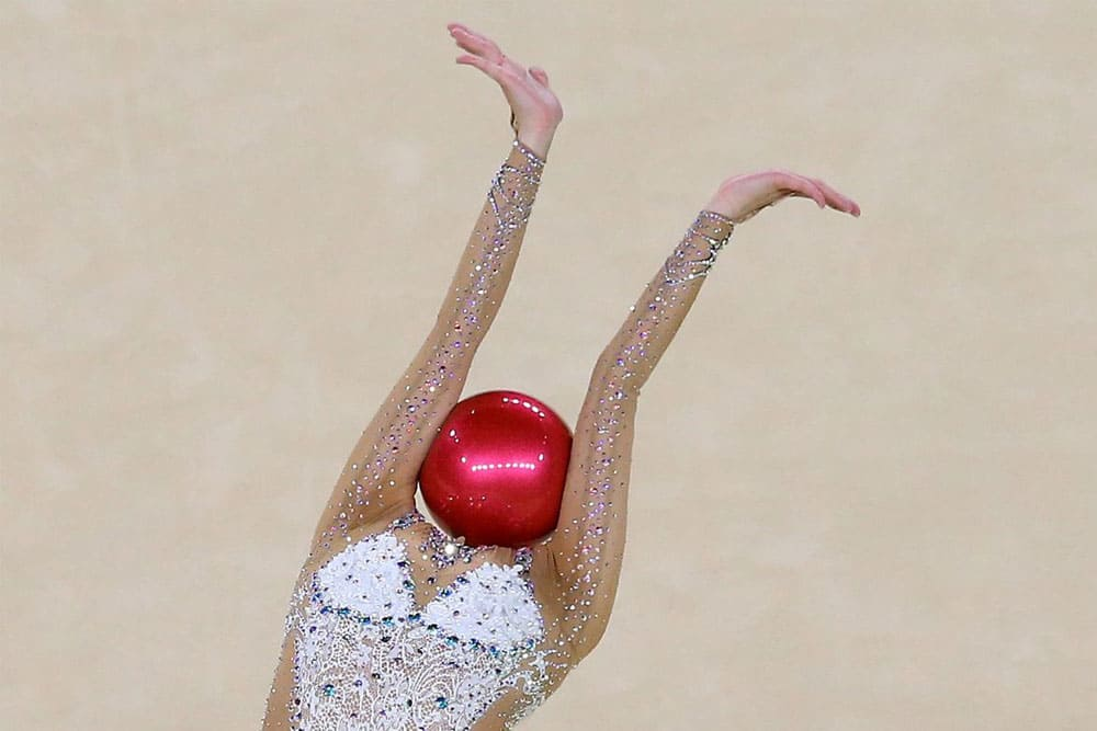 Rhythmic gymnast with a ball in place of her head