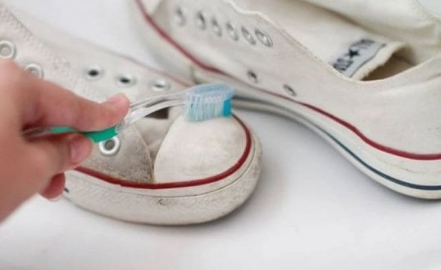 Cleaning white shoes with a toothbrush and toothpaste
