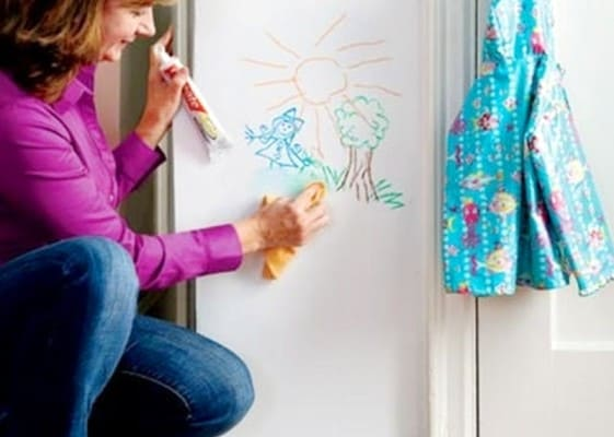 A mother using toothpaste to get crayon off of the wall