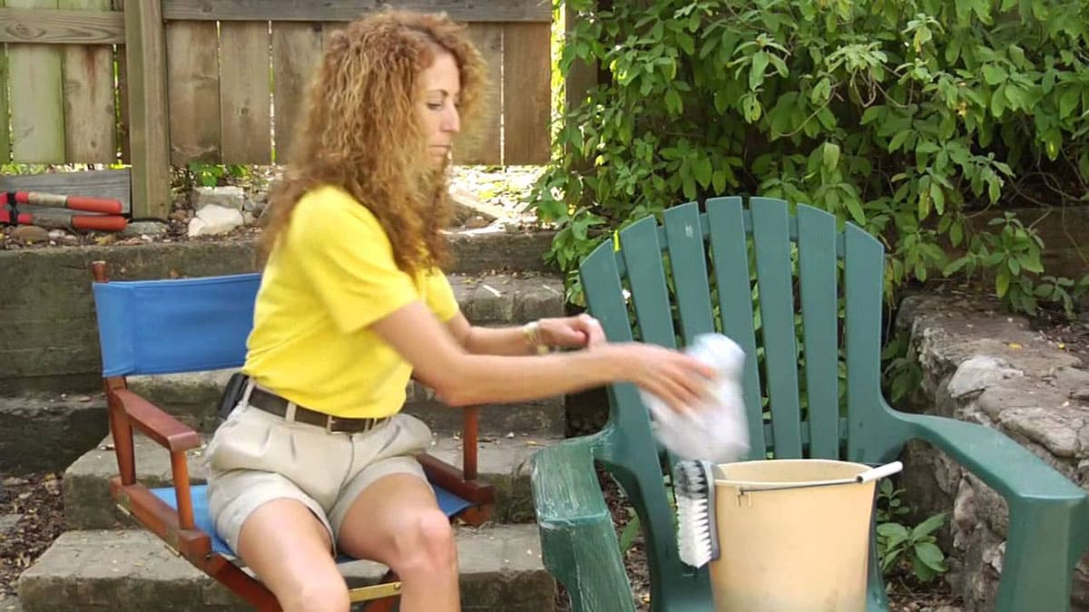 A woman cleaning a chair outside