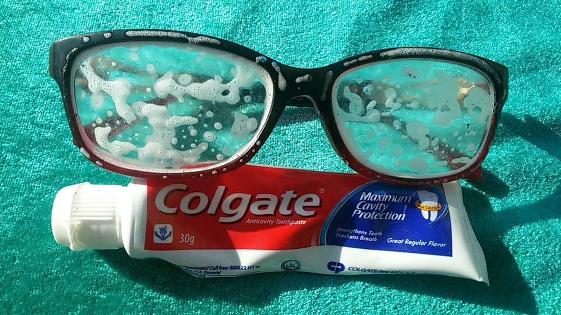 A tube of toothpaste under a pair of glasses