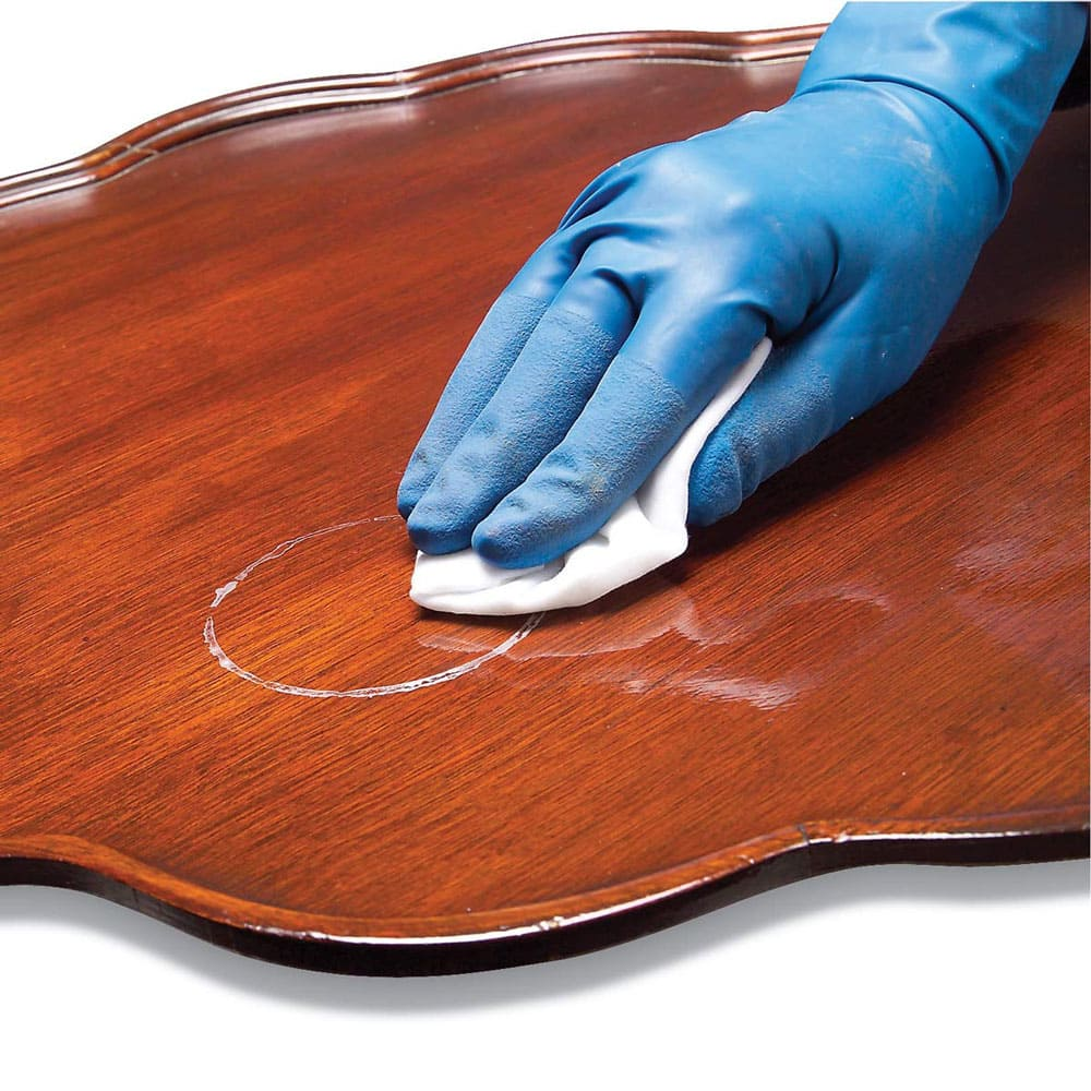 A gloved hand cleaning a coffee table.