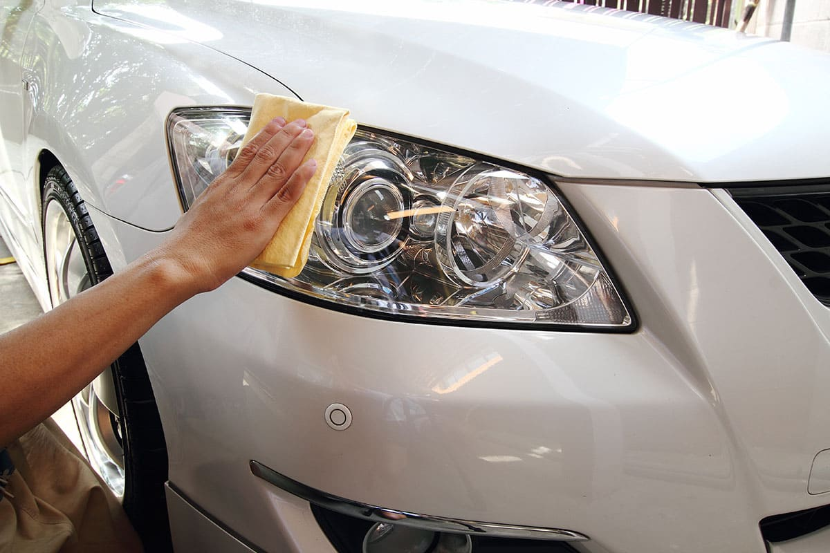 A shiny headlight being cleaned