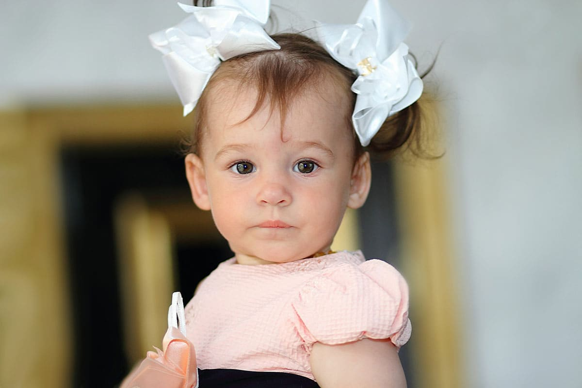 A baby with two bows in her hair