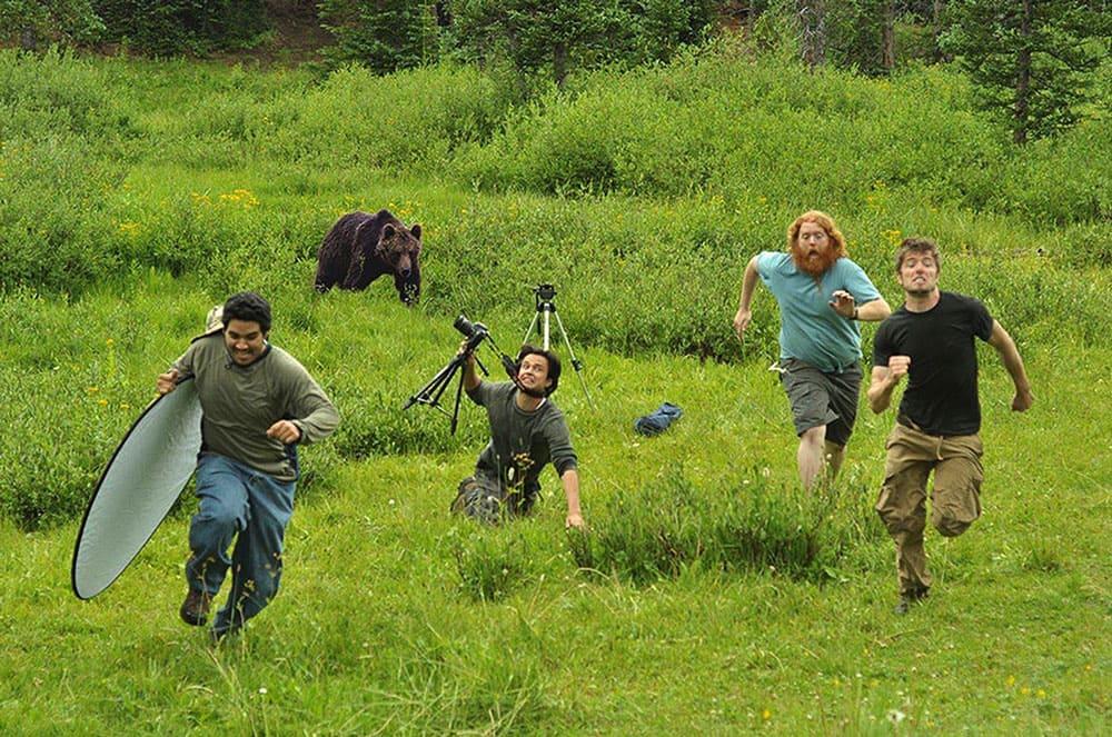 A bunch of photographers running away from a bear.