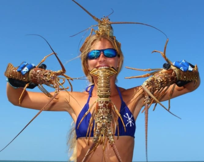 A woman holding a bunch of lobsters